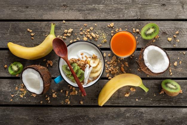 Kokos-joghurt-früchte mit müsli serviert auf holztischplatte. probiotisches lebensmittelkonzept. leckeres und gesundes frühstück