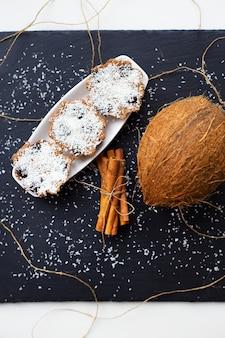 Kokos-muffins mit schokolade auf schwarzem hintergrund und ganzer kokosnuss, nahaufnahme