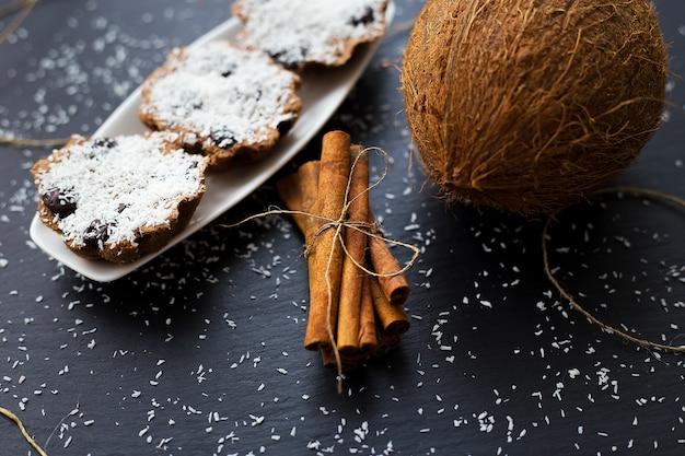 Kokos-muffins mit schokolade und zimt auf schwarzem hintergrund und ganzer kokos