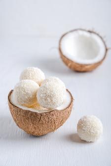 Kokos vegane süße trüffel mit einer quarkfüllung serviert in halber frischer kokosnuss auf einem tisch