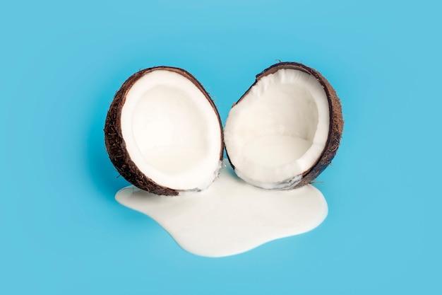 Kokoscreme oder butter mit frischen kokosnüssen auf einem blauen hintergrund. weißer sahnesaft tropft von der kokosnuss.