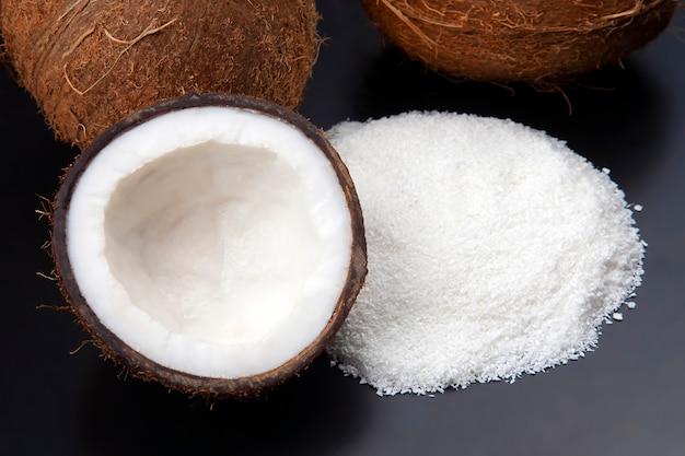 Kokosflocken auf einem dunklen hintergrund neben einer kokosnuss. vitaminfrüchte. gesundes essen