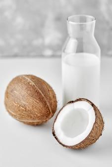Kokosmilch in der glasflasche und in den frischen kokosnüssen mit hälfte auf grau