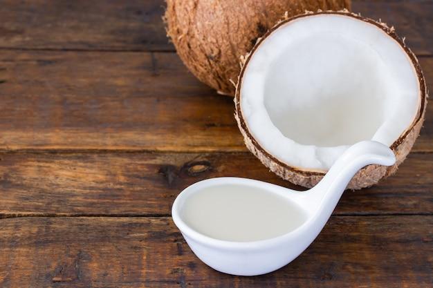 Kokosmilch und halbe kokosnuss auf holzschreibtisch