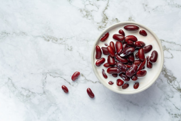 Kokosmilchdessert der roten bohne im weißen schüsselplatz auf weißem marmorboden