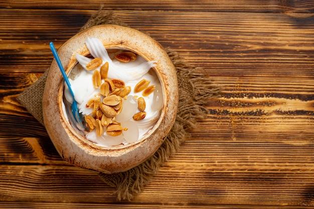 Kokosmilcheis in der kokosnussschale auf der dunklen holzoberfläche