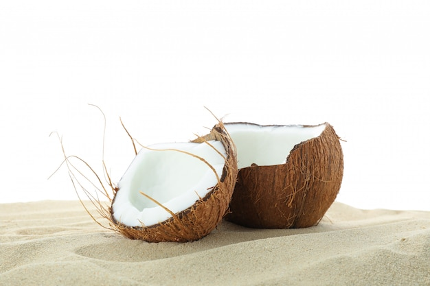 Kokosnüsse auf klarem meersand lokalisiert auf weißem hintergrund. sommerurlaub
