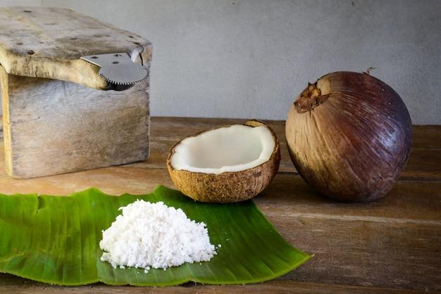 Kokosnüsse und kokosflocken auf bananenblatt und kokosraspel