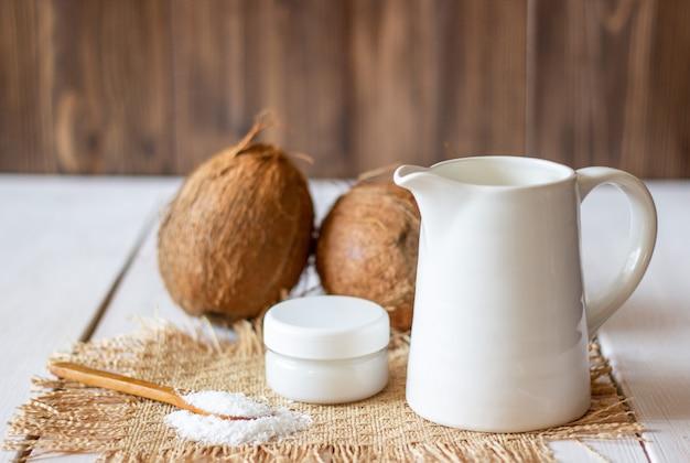 Kokosnüsse und kokosmilch in einem metalltopf. holzuntergrund.