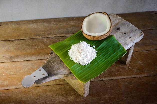 Kokosnüsse und kokosnussflocken auf bananenblatt- und kokosnussreibe