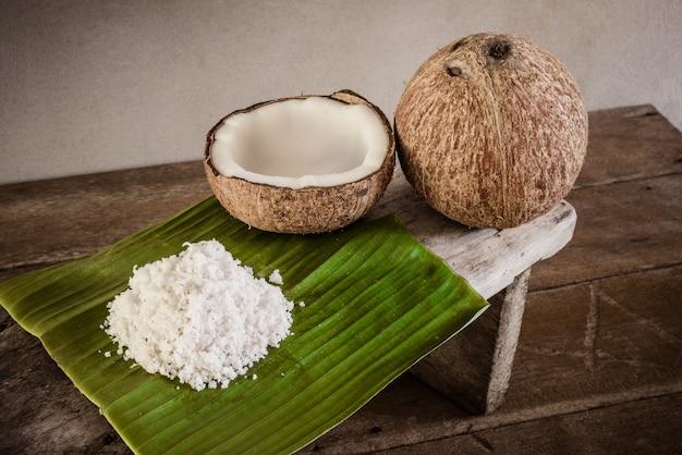 Kokosnüsse und kokosnussflocken auf bananenblatt und kokosraspel