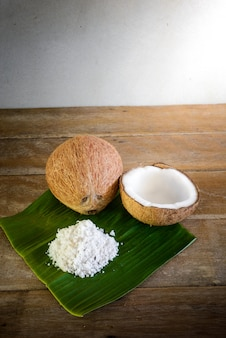 Kokosnüsse und kokosnussflocken auf bananenblatt