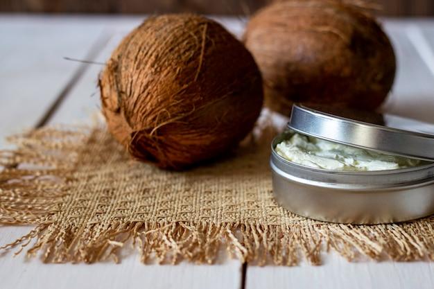 Kokosnüsse und kokosöl in einem metalltopf. holzuntergrund.