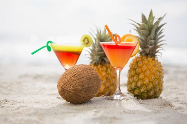 Kokosnuss, ananas und zwei gläser cocktail trinken gehalten auf dem sand