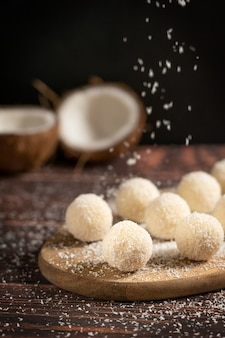Kokosnuss-bio-süßtrüffel mit streuseln von kokosraspeln, serviert auf dunkelbraunem holztisch
