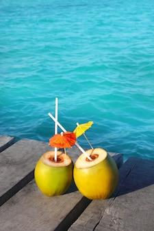 Kokosnuss coktails in karibischen meeren auf hölzernem pier