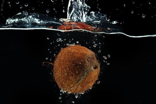 Kokosnuss, die in das wasser mit einem spritzer gegen schwarzen hintergrund nah oben fällt