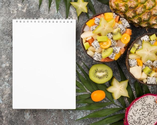 Kokosnuss gefüllt mit obstsalat und leerem notizblock