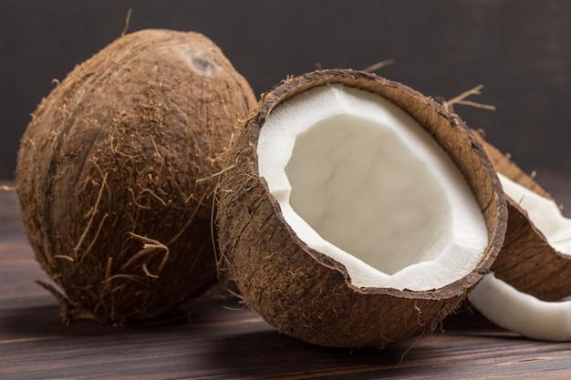 Kokosnuss, in halbe kokosnuss auf dunklem hölzernem hintergrund gehackt.