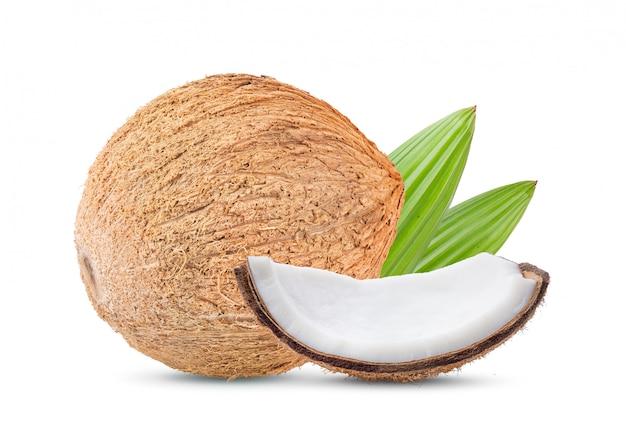 Kokosnuss mit blättern auf weißer wand.