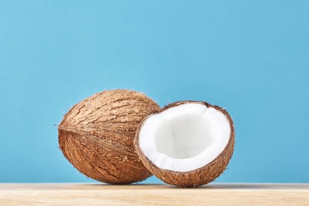 Kokosnuss mit hälfte auf holztisch gegen blauen hintergrund