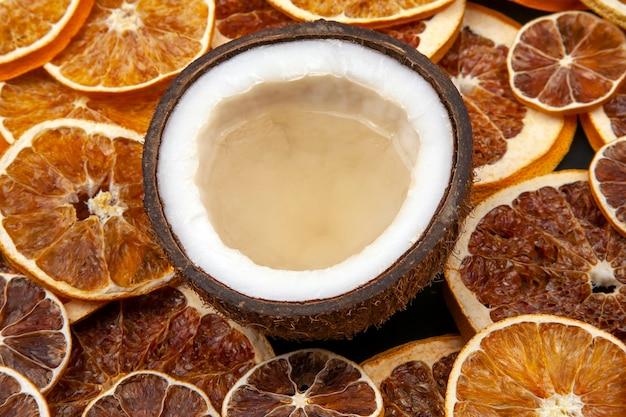 Kokosnuss mit natürlicher milch auf einem hintergrund von getrockneten zitrusfrüchten