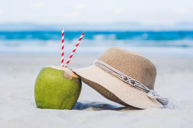 Kokosnuss mit stroh im sand am strand.