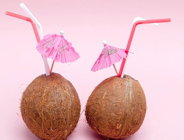 Kokosnuss mit trinkhalm und regenschirm an rosa wand.