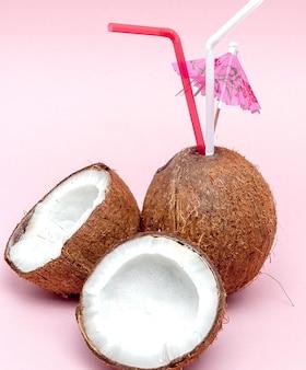 Kokosnuss mit trinkhalm und regenschirm auf rosa hintergrund mit kopienraum.