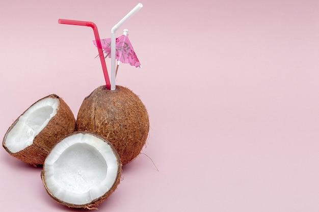Kokosnuss mit trinkhalm und regenschirm auf rosa wand mit kopierraum.
