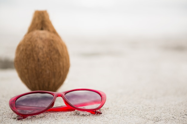 Kokosnuss und eine sonnenbrille gehalten auf dem sand