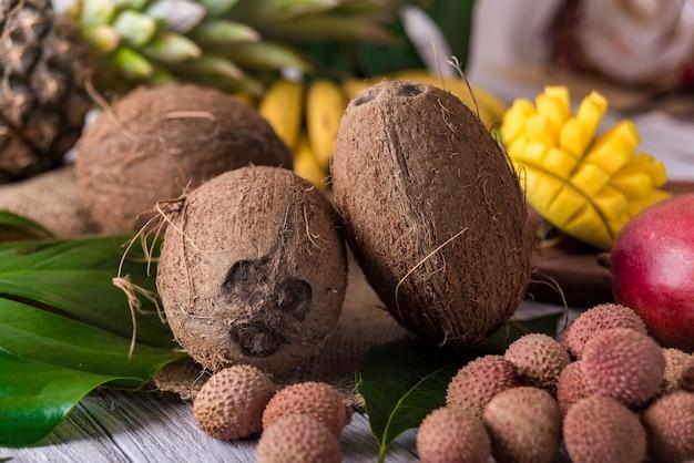 Kokosnuss und exotische früchte auf holztisch.