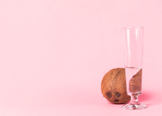 Kokosnuss und glas wasser auf rosa hintergrund