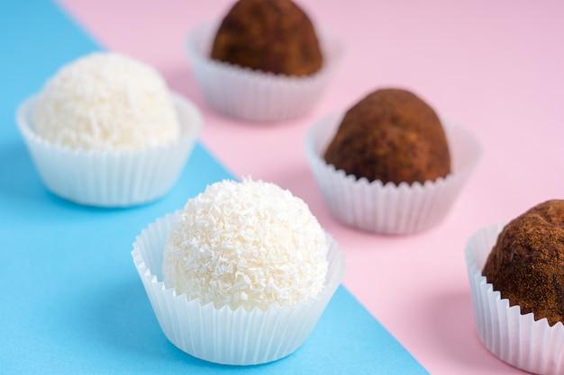 Kokosnuss- und kakaonuss-trüffel oder hausgemachte energiekugeln auf buntem rosa und blauem hintergrund