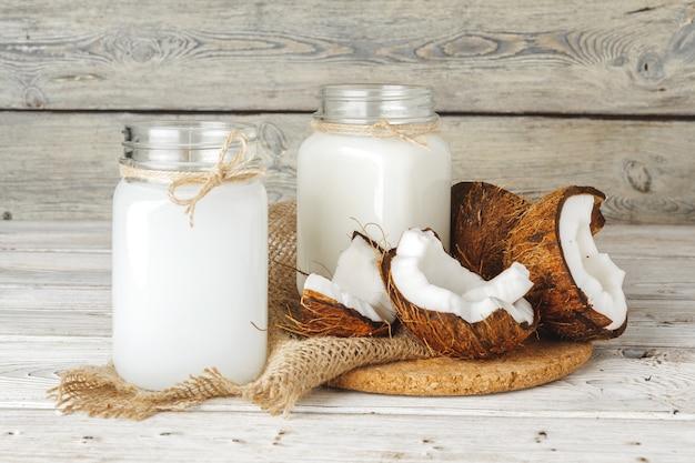 Kokosnuss und kokosmilch auf rustikalem holztisch