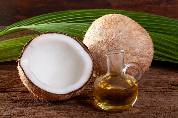 Kokosnuss- und kokosnussöl auf hölzernem hintergrund.