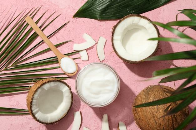 Kokosnuss und kosmetik auf rosa draufsicht