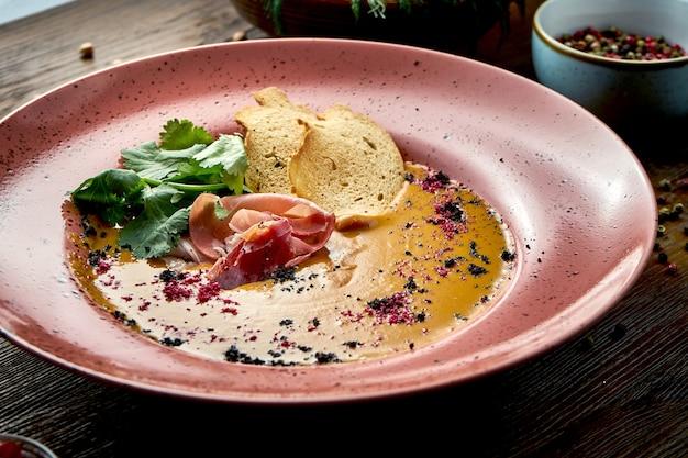 Kokosnuss- und linsencremesuppe mit croutons und jamon in einer roten platte auf einem hölzernen hintergrund.