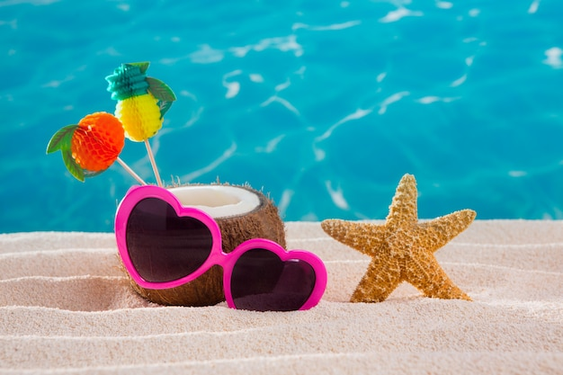 Kokosnusscocktail auf tropischer sandstrandherzsonnenbrille
