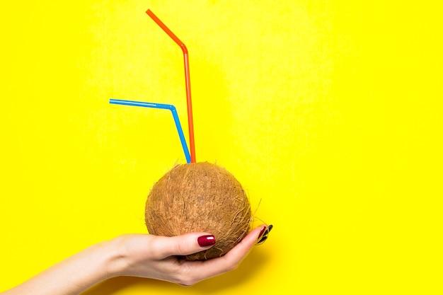Kokosnusscocktail in der kokosnuss in den weiblichen händen nahaufnahme auf einem gelben mit platz für text.