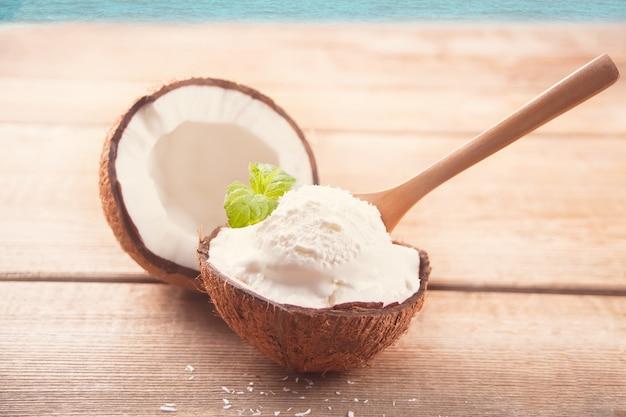 Kokosnusseis auf dem holztisch mit tadellosem blatt