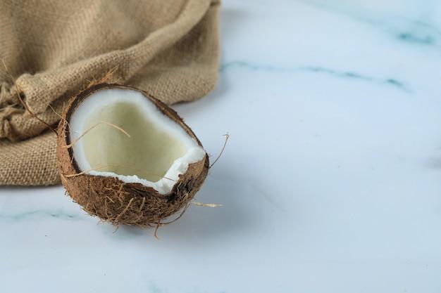 Kokosnussfrucht auf einem blauen marmor mit sackleinen