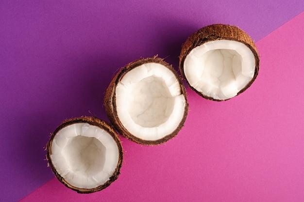 Kokosnussfrüchte in reihe auf violettem und purpurrotem einfachem hintergrund, tropisches konzept des abstrakten lebensmittels, draufsicht