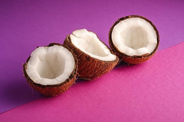 Kokosnussfrüchte in reihe auf violetter und purpurroter einfacher wand, tropisches konzept des abstrakten lebensmittels, winkelansicht