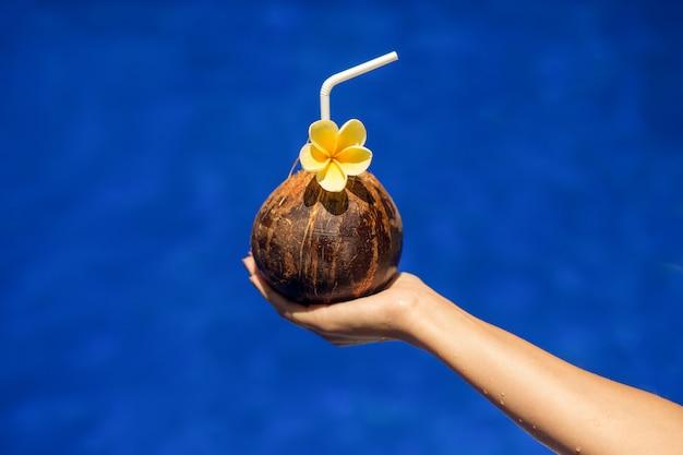 Kokosnussgetränk in der frauenhand auf schwimmbad