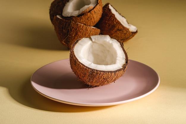 Kokosnusshälfte in rosa platte mit nussfrüchten auf cremegelber ebener oberfläche, tropisches konzept des abstrakten lebensmittels, winkelansicht