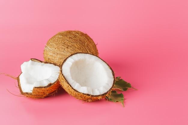 Kokosnusshälften auf einem hellen rosa