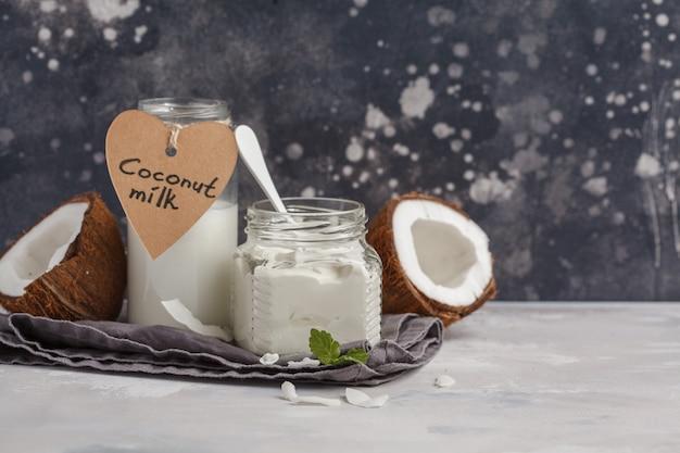 Kokosnussjoghurt und kokosmilch in einem glasgefäß. gesundes lebensmittelkonzept des strengen vegetariers, dunkler hintergrund, kopienraum