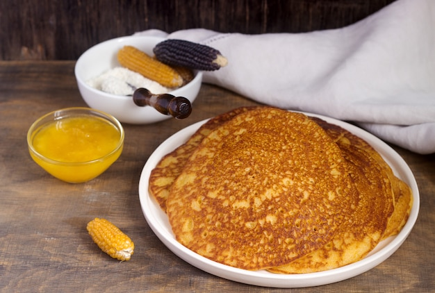 Kokosnussmaispfannkuchen mit honig. rustikaler stil.