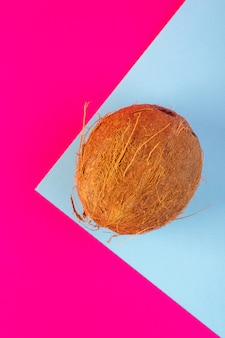 Kokosnussnüsse von oben in scheiben geschnitten und ganz milchig frisch ausgereift auf dem rosa und eisblau isoliert